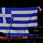 Demetrios Kastaris holds up the Greek flag with Yiannis Economides, at the Katharí debut concert at Flushing Town Hall, Flushing Queens, New York, December 10, 2010, photo by Norm Harris.