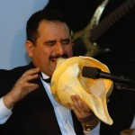 "Demetrios performs melodies on an extra large conch shell. Percussionist, Angel Rodriguez on the right. Kyklos, Circle of Glory Event ""An Evening of Olympic Celebration"" at the Newington-Cropsey Foundation, Olympic Art Work of Euripides Kastaris, Hastings on Hudson, New York, March 20, 2004."