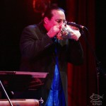 Steve Turre playing two conch shells simultaneously and in harmony, Queens Theatre in the Park, Flushing, New York, December 17, 2004, photo by Jerry Lacay.