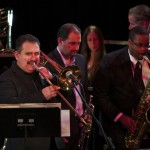 Front three musicians, left to right,  Demetrios Kastaris, trombone, Yiannis Economides, trumpeter from Thessaloniki, Greece, Melvin Smith, tenor saxophone.  Back row, left to right, Ray Campos, bass trombone, Connie Grossman, flute, Robert Thomas, violin. Flushing Town Hall, Flushing Queens, New York, December 10, 2010, photo by Norm Harris.